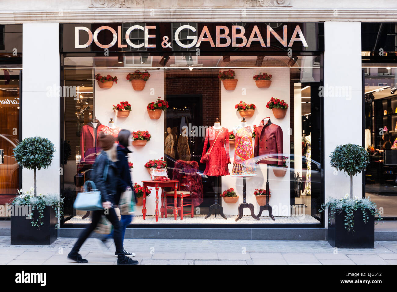 A couple of young women walk by the Dolce & Gabbana  fashion store on Old Bond Street, Mayfair, London, England. - Stock Image