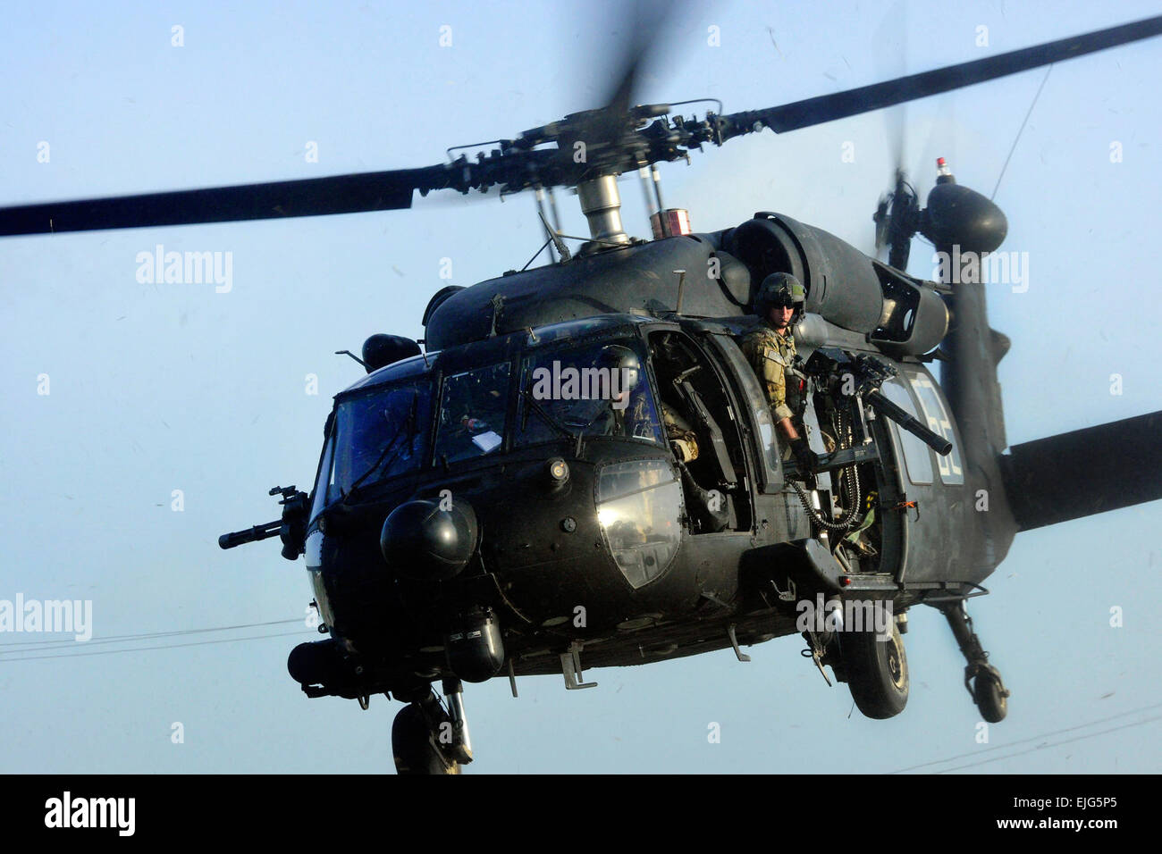 A U.S. Army crew chief observes the horizon from the side door of a UH-60 Black Hawk helicopter as they prepare - Stock Image