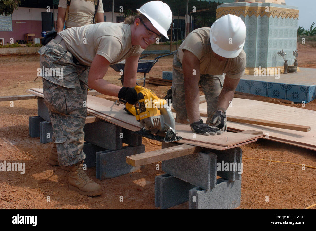 Pvt. 1st Class Michelle Almeida of Kihei, Hawaii and Sgt. 1st Class Brandon Cabanilla of Kahalui cut wood framing - Stock Image