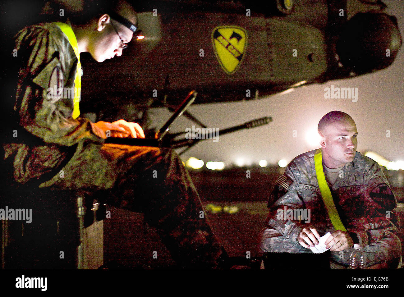 Working under a night sky, U.S. Army Sgt. Derrick Douglas, right, and Spc. Nicholas Kirckof, left, review aircraft logs to plan the night's work load on Camp Beurhing, Kuwait, May 5, 2009. Douglas and Kirckof, both AH-64D Apache attack helicopter crew chiefs, are assigned to the 1st Cavalry Division's Company B, 4th Attack Reconnaissance Battalion, 227th Aviation Regiment, 1st Air Cavalry Brigade.  Sgt. Travis Zielinski Stock Photo