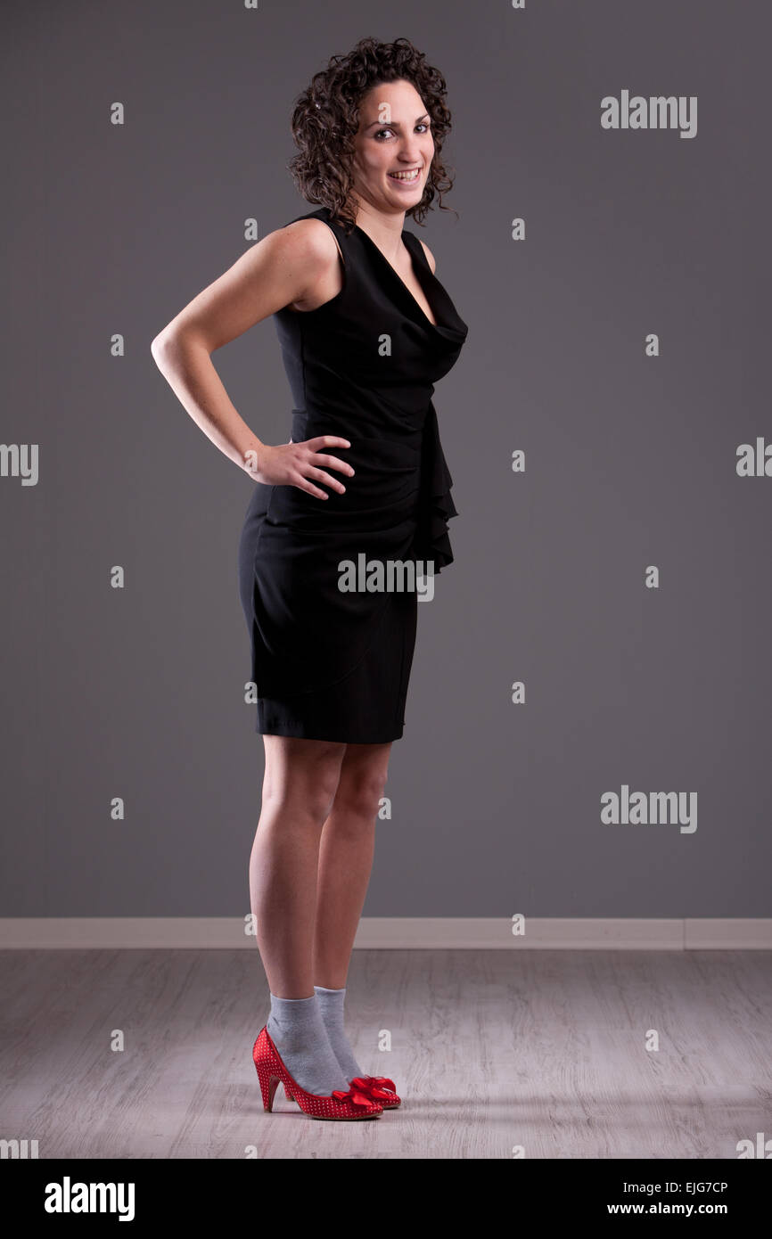 Curly Haired Smiling Woman In Grey Socks And Red Shoes Wearing A