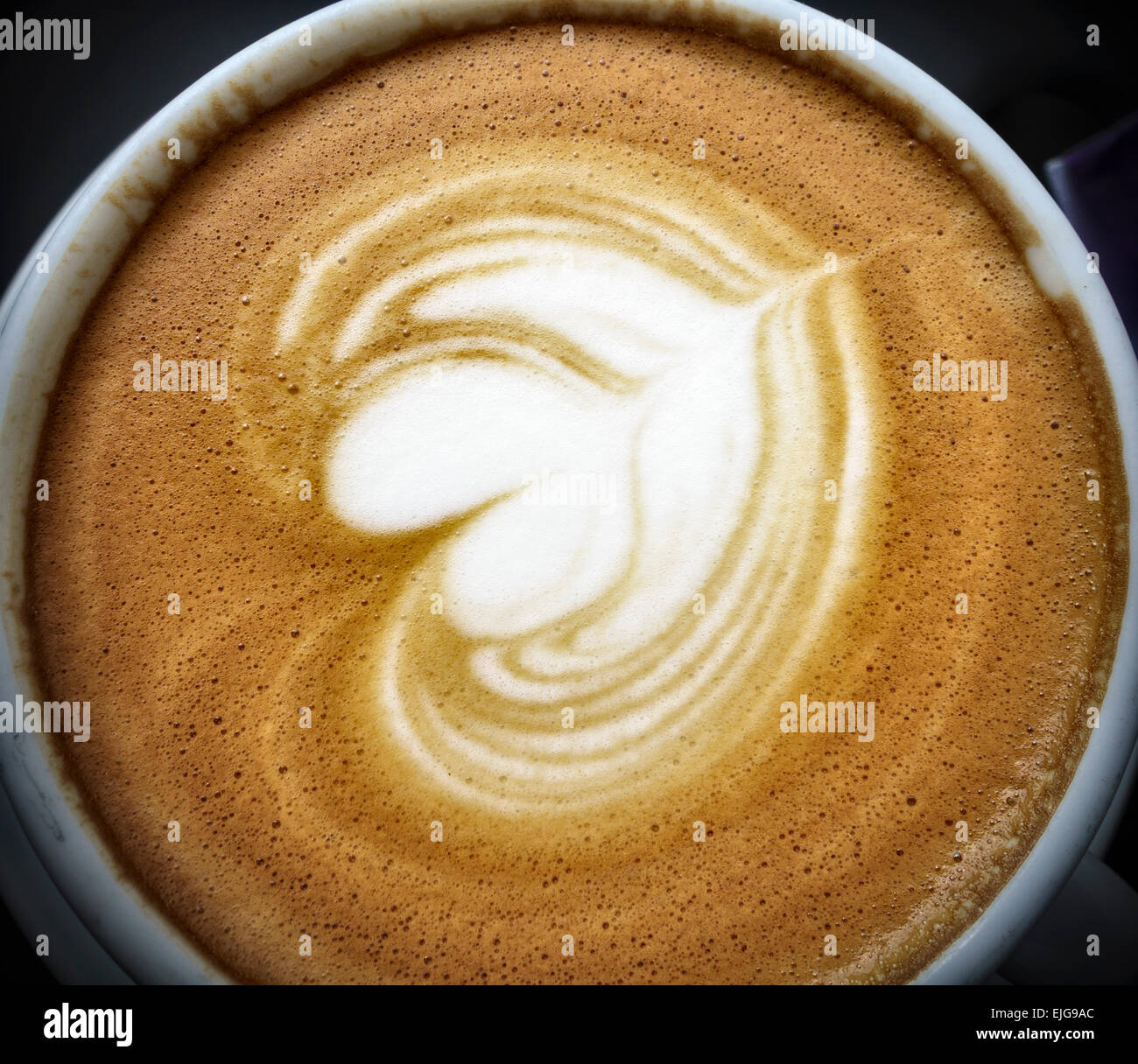 Closeup of the froth on a cappuccino in a china cup - Stock Image
