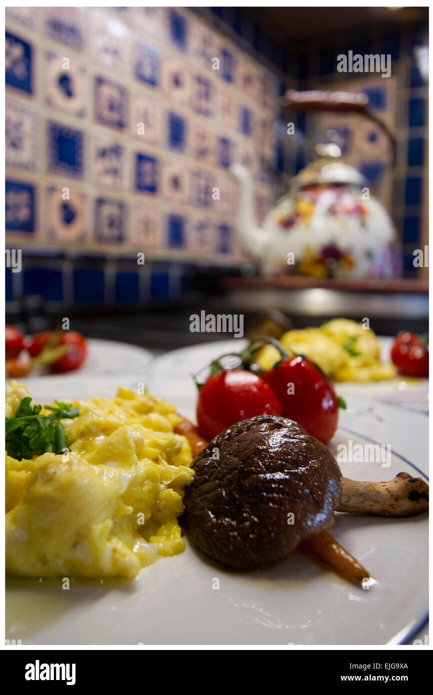 Mushrooms with scramble eggs and cherry tomato, hongos  con huevos revueltos   y tomate, kettle, blue background, - Stock Image