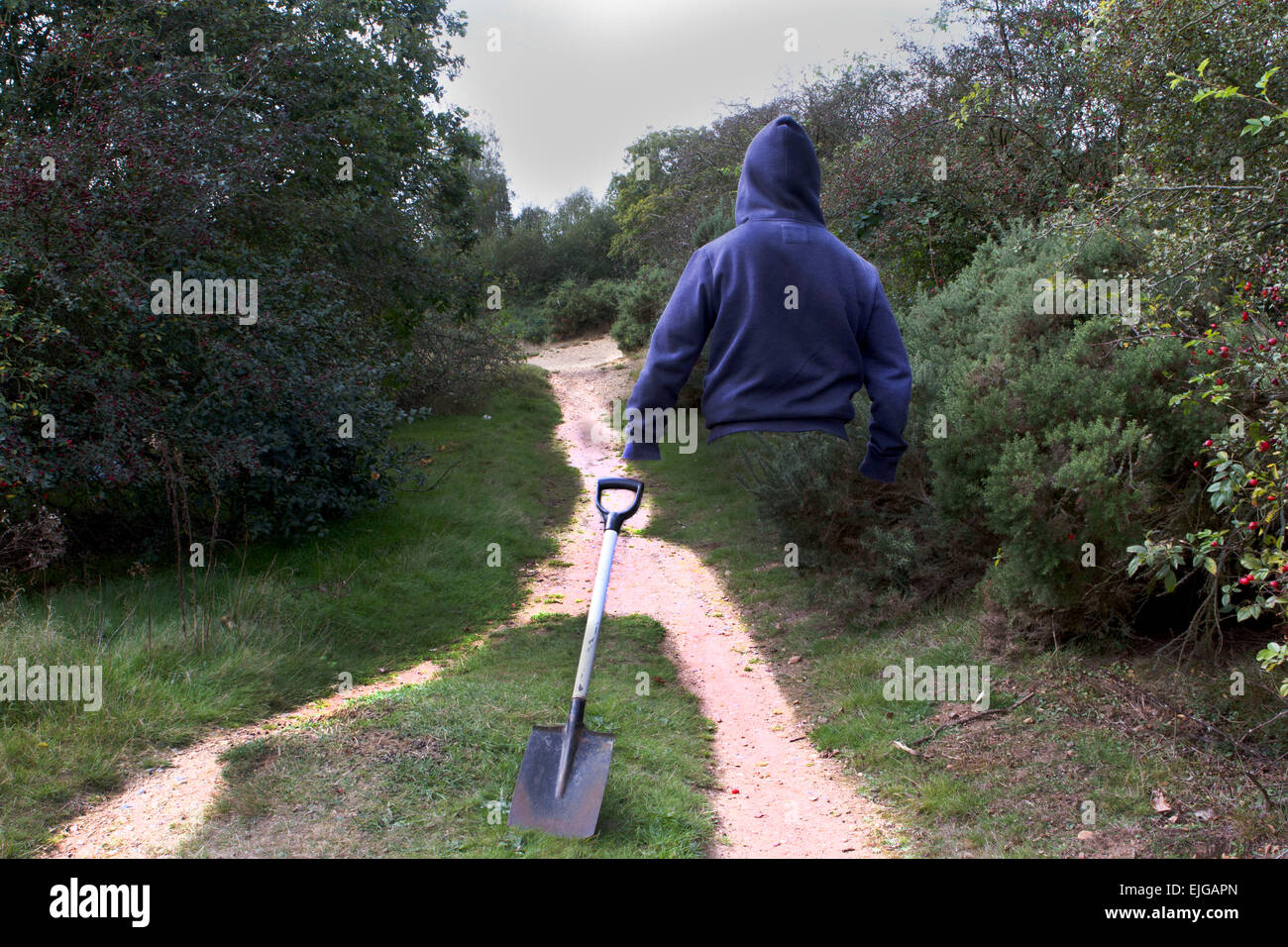 choosing the right way, cojiendo el camino correcto , mystery man with a shovel,  hombre con una pala, man walking - Stock Image