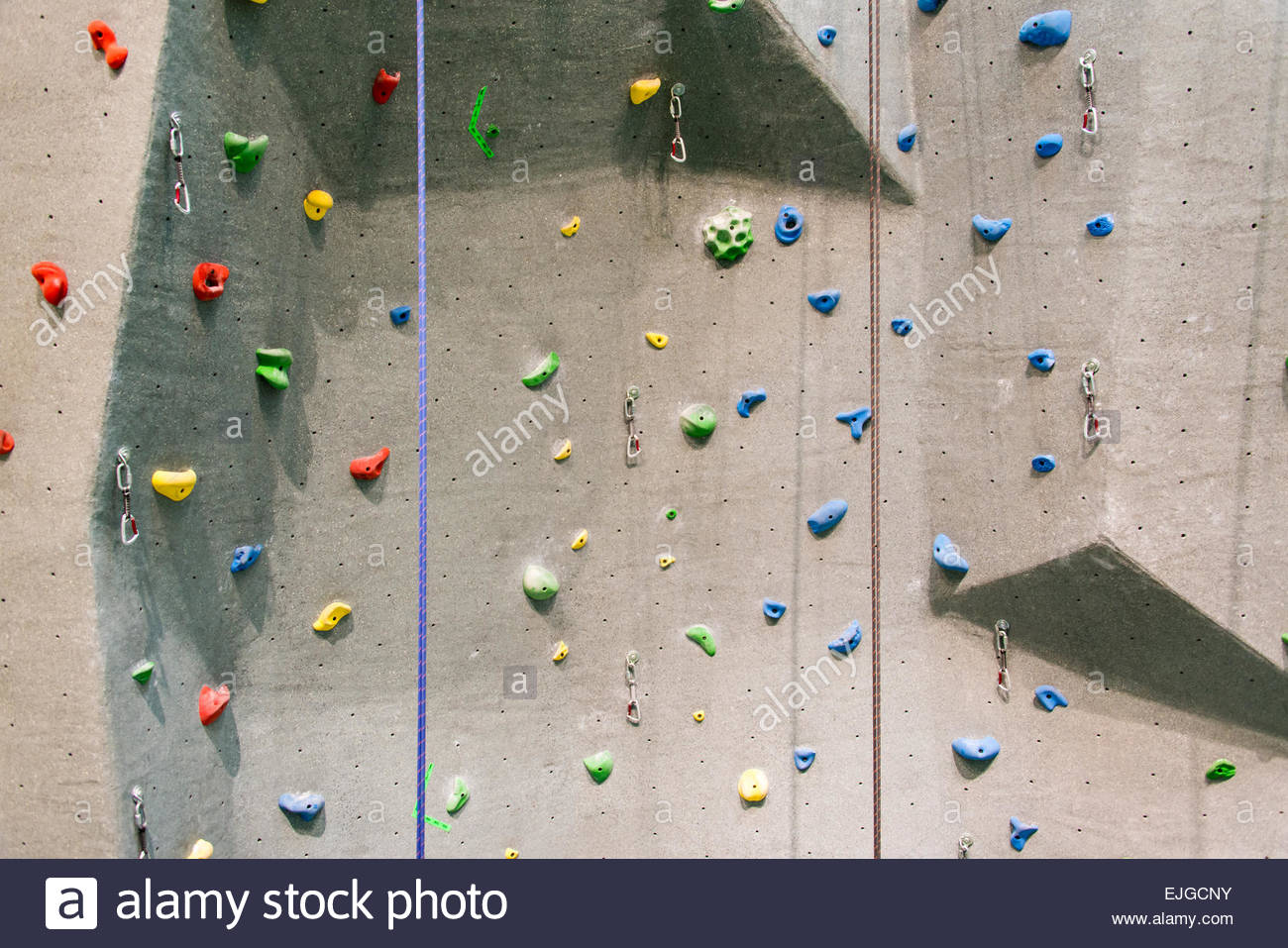 Indoor rock climbing wall in a sport facility where many practice to be fit and in better health - Stock Image