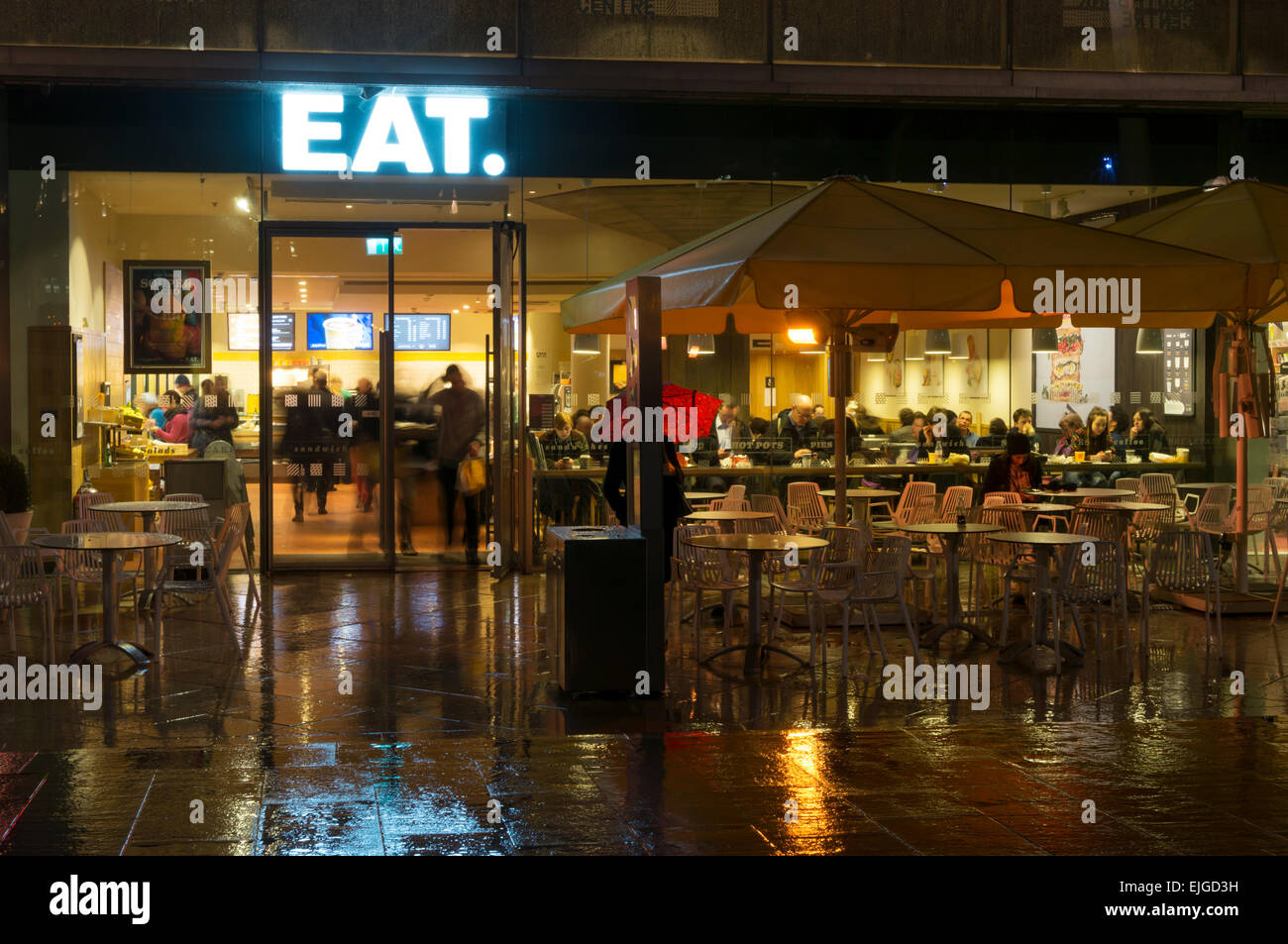 Branch of Eat sandwich shop on the Southbank in London at night in the rain. - Stock Image