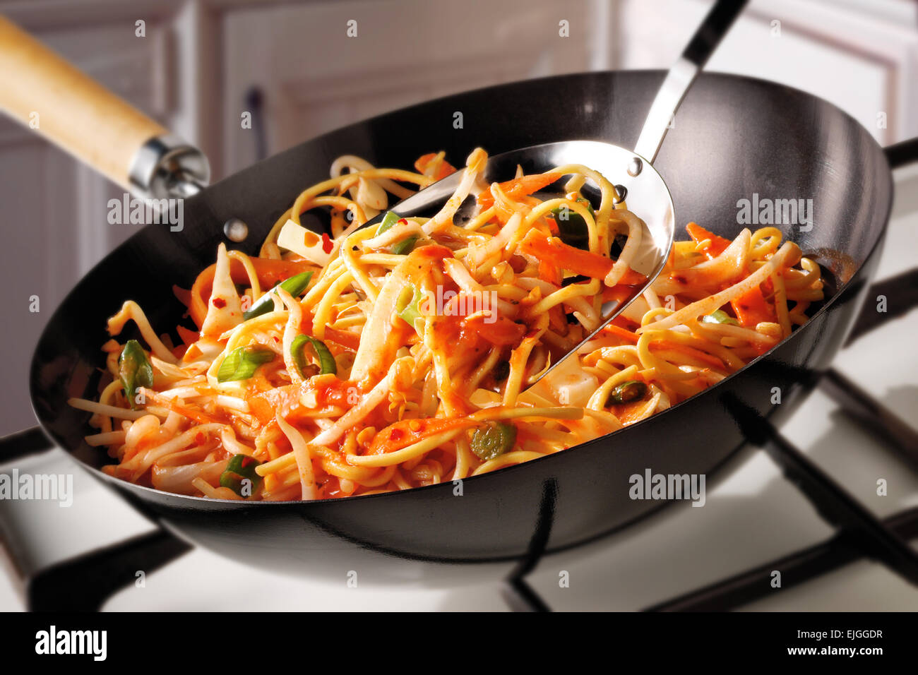 Stir Fry Noodles, carrots & Bean Shoots being cooked - Stock Image