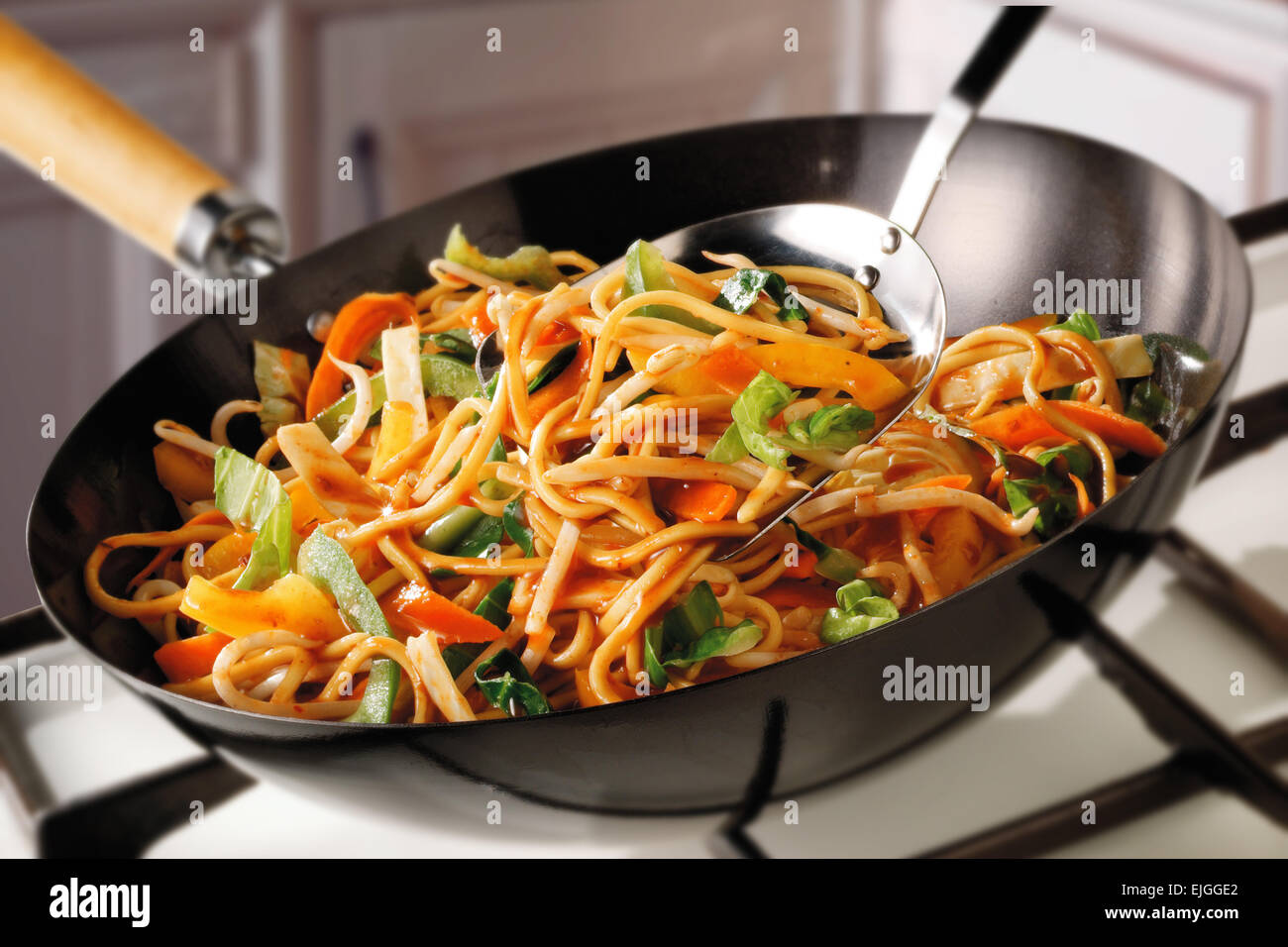Stir Fry Noodles, pak choi, carrots & bean shoots being cooked - Stock Image