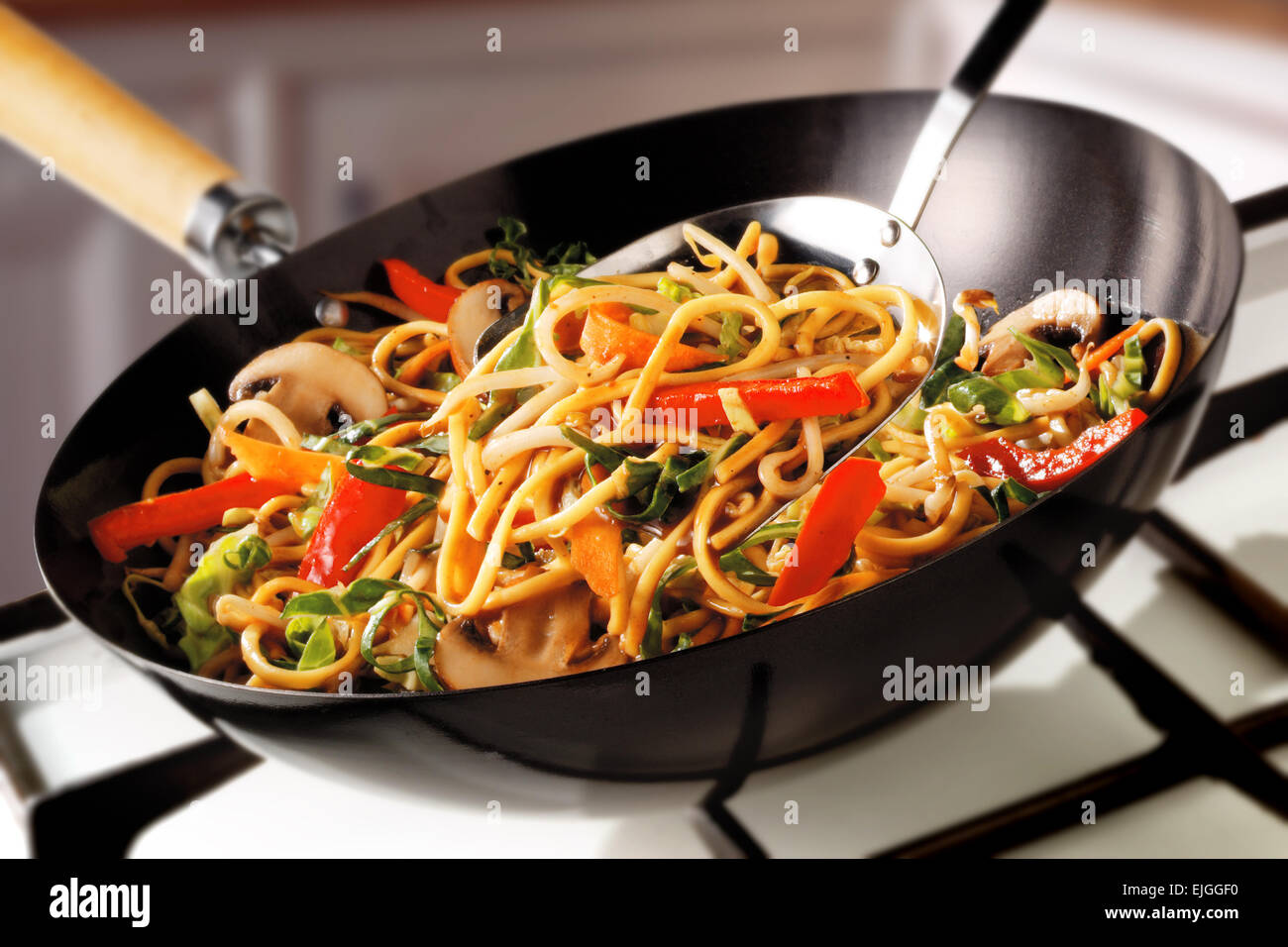 Stir Fry Noodles, peppers, mushrooms & carrots being cooked - Stock Image