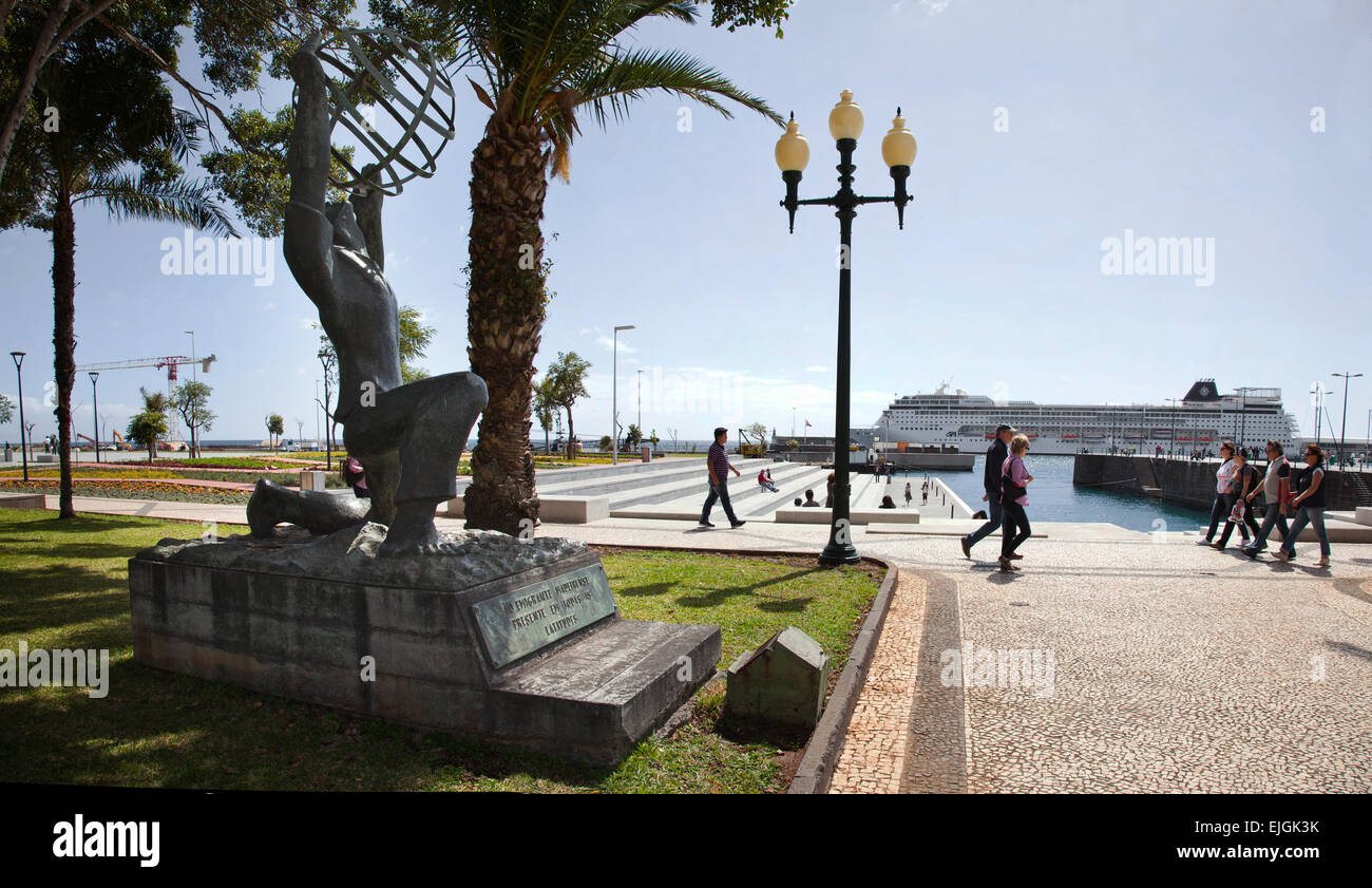 Emigrant Memorial Statue on the promenade at Funchal Madeira Portugal with tourists walking and a cruise ship in - Stock Image
