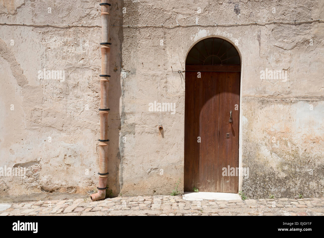 Door and terracotta drainpipe on a medieval building in Cefalu Sicily - Stock Image