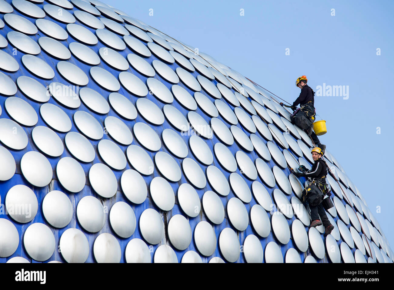 Workmen cleaning the decorative discs on the exterior of the Selfridges building in Birmingham - Stock Image