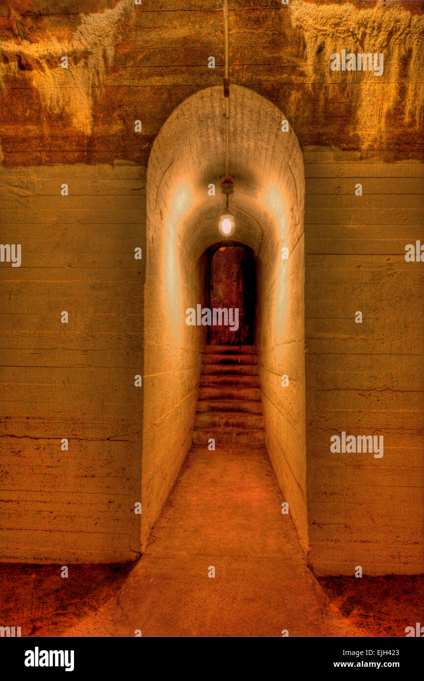 A narrow foreboding tunnel with steps at end. - Stock Image