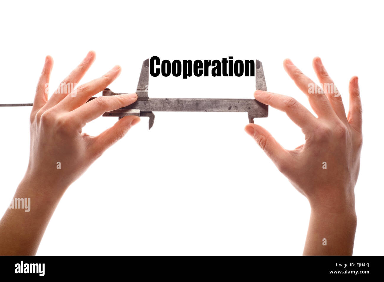 """Color horizontal shot of two hands holding a caliper and measuring the word """"cooperation"""". Stock Photo"""