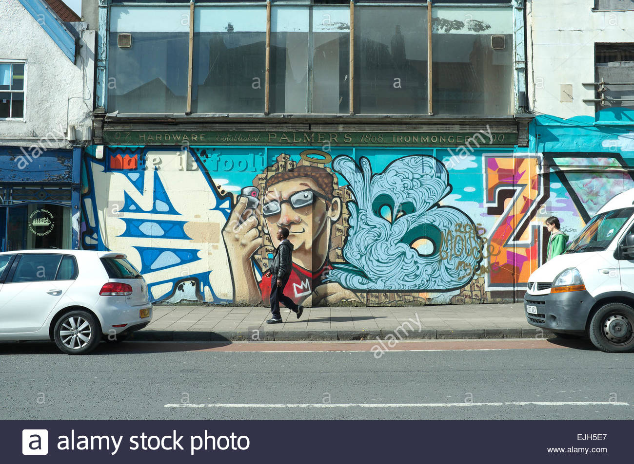 Stokes Croft - a pedestrian strolls pass a former hardware store, now covered in street art, in Stokes Croft, Bristol, - Stock Image