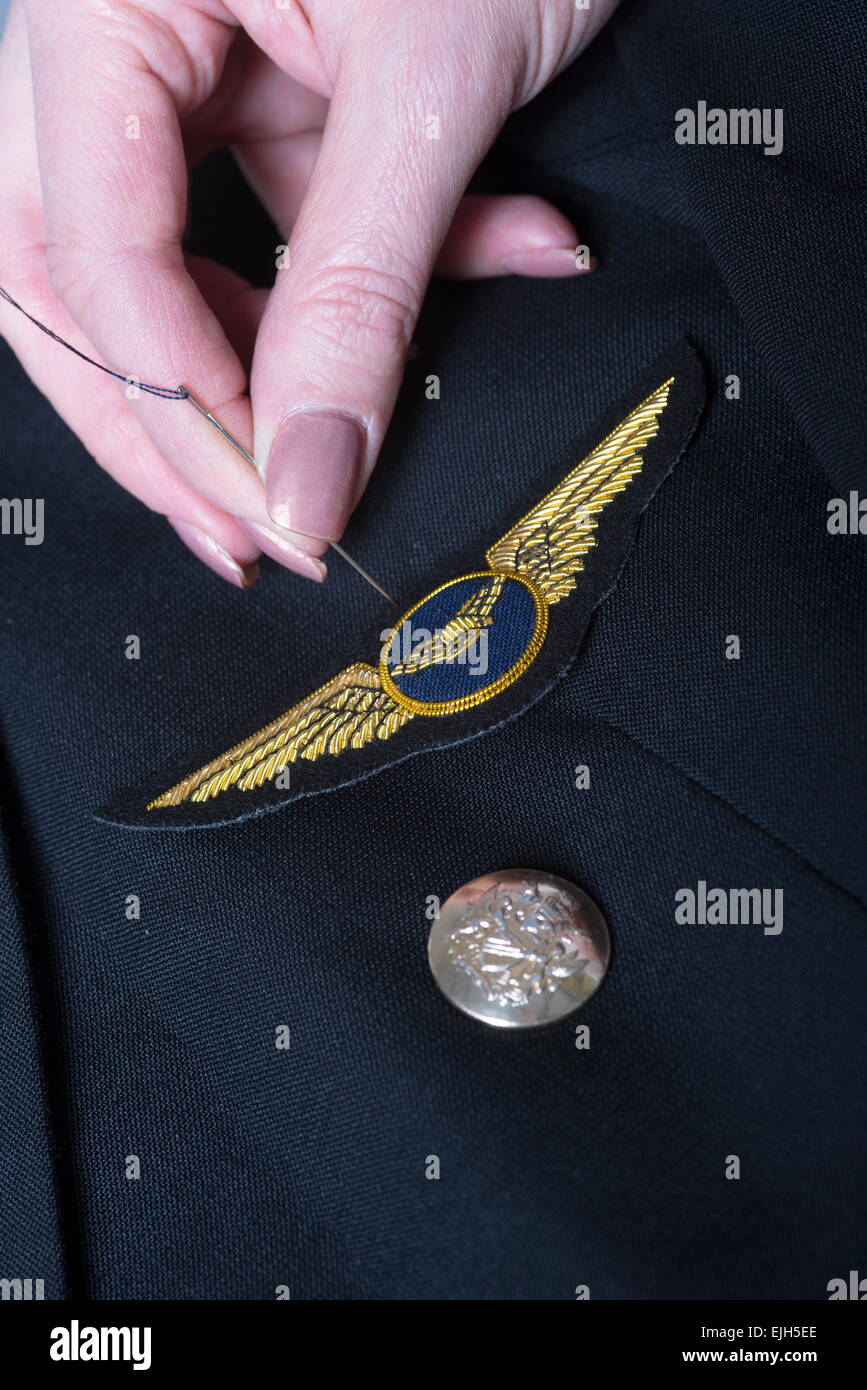Sewing an airline pilots wings onto a uniform jacket - Stock Image
