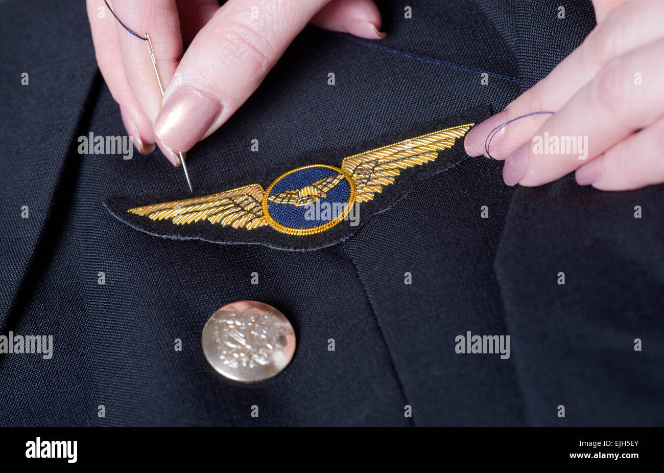 Sewing an airline pilots wings onto a uniform jacket Stock Photo