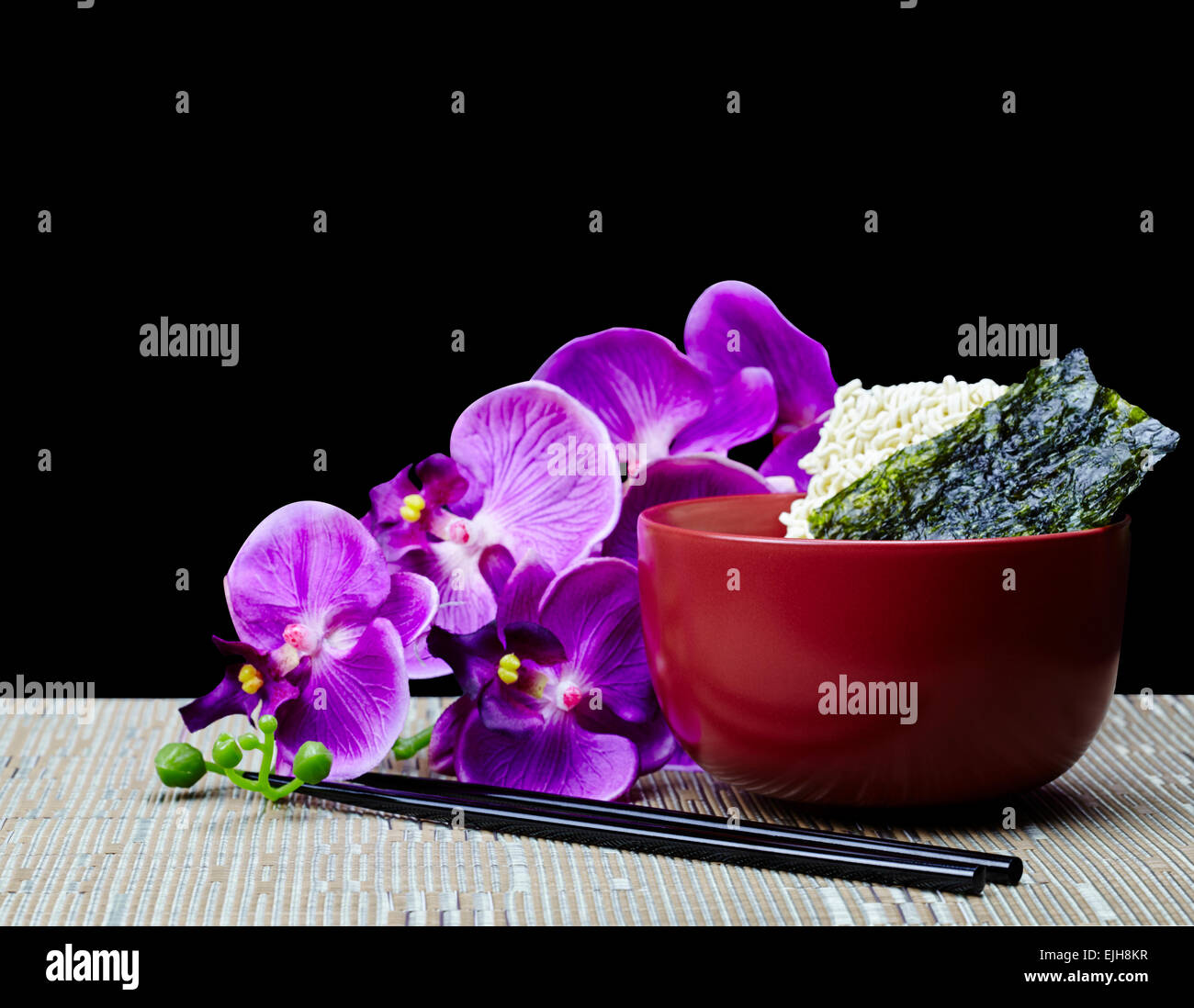 Oriental Saimin Noodles with Japanese Nori Seaweed and Chopsticks with Hawaiian Orchid Flower Isolated on Black - Stock Image