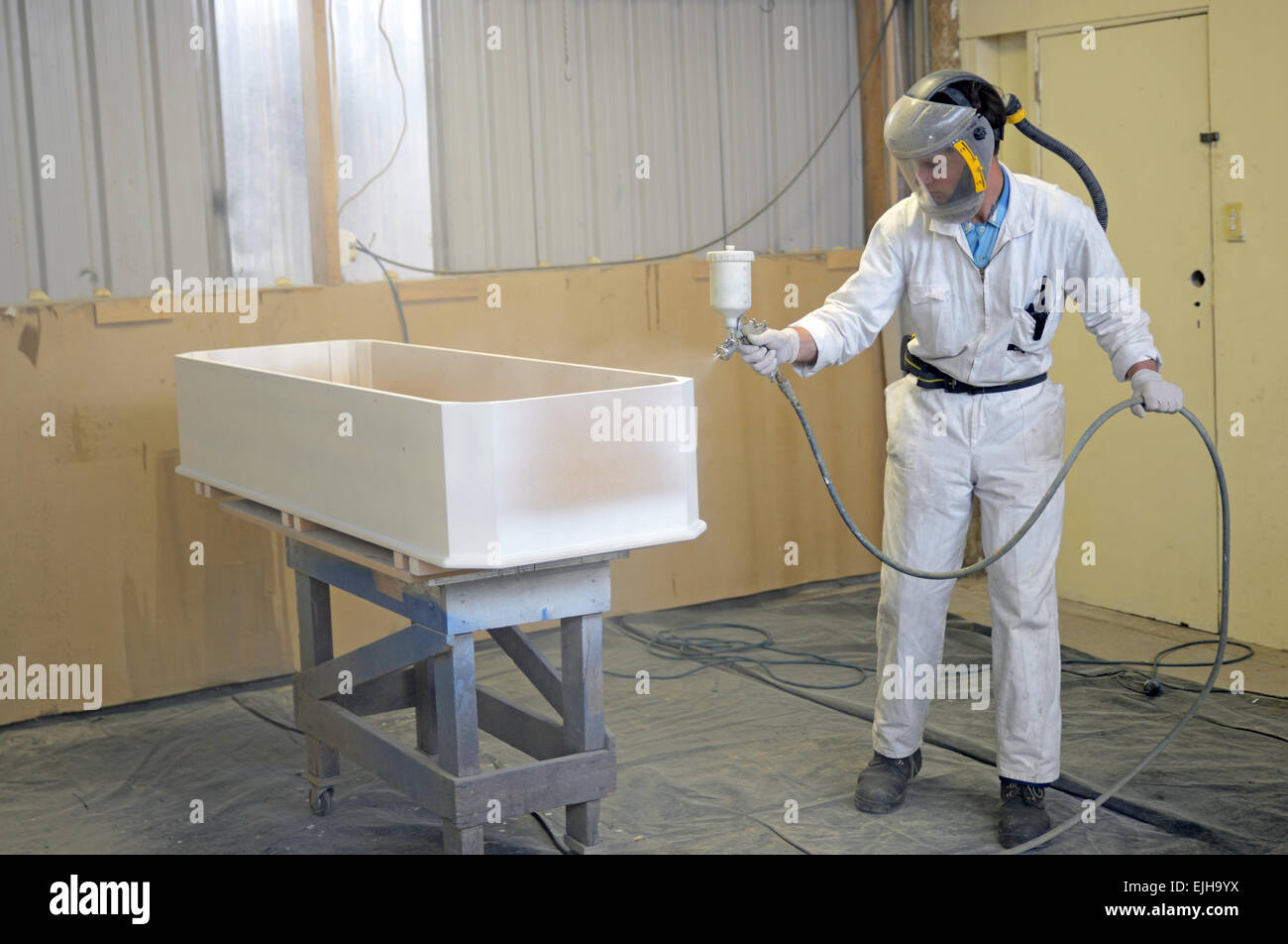 A tradesman spray paints a coffin in a spray booth - Stock Image