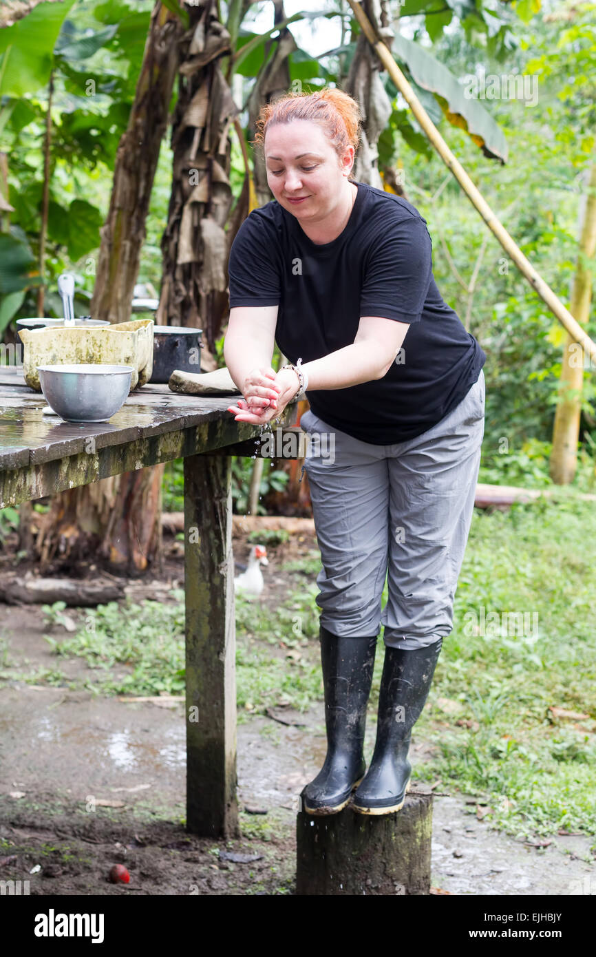Tourist Washing Her Hand In Typical Indigenous Environments - Stock Image
