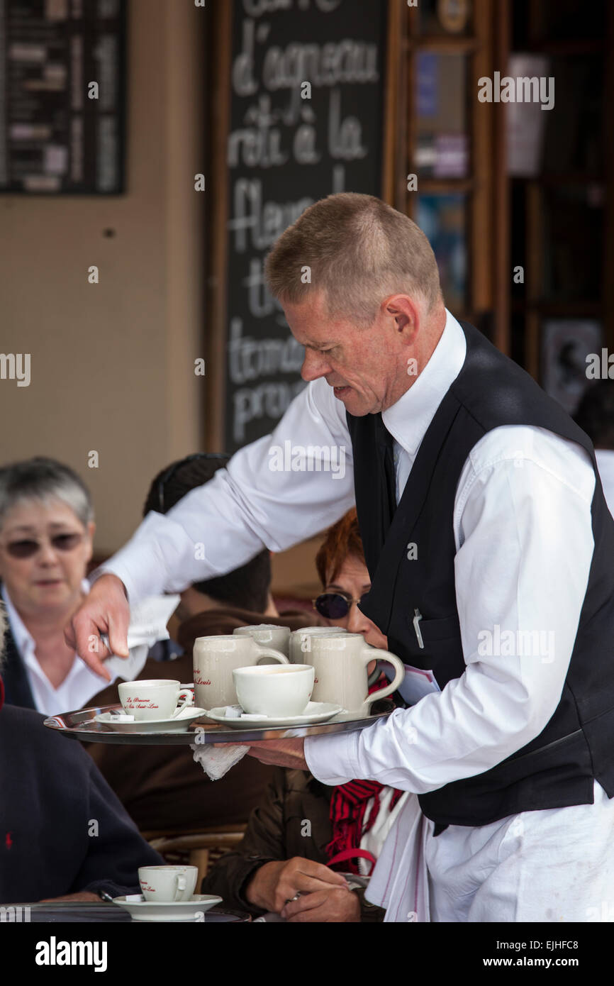Waiter serves coffee at outdoor table, Paris, France - Stock Image