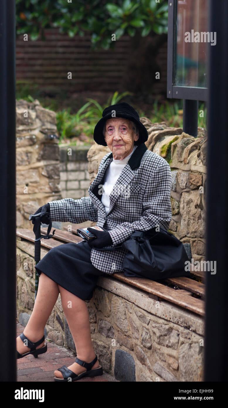 Elderly lady on bench, Godalming, Surrey, England - Stock Image