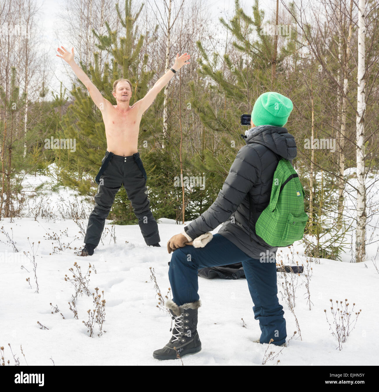 Young man, stripped to the waist, standing on snow and posing for the photographer. - Stock Image