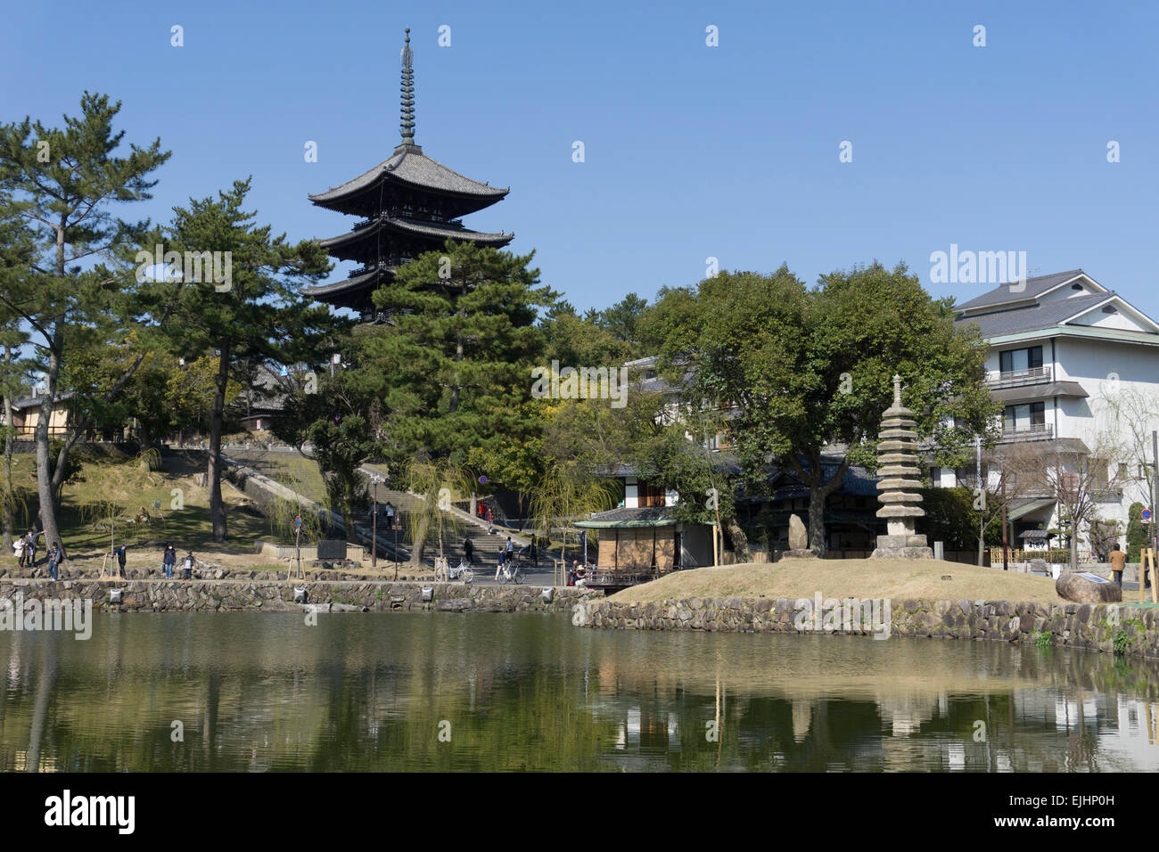 Japanese pagoda tower above trees at Kofukuji temple in Nara, Japan. In the foreground is a small restaurant on - Stock Image