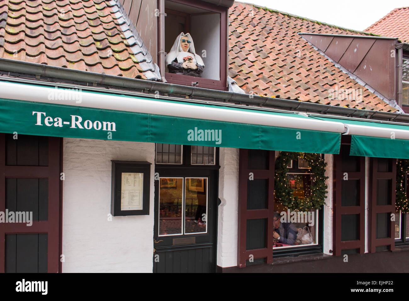 Dummy woman looking from window of tea room, Bruges, Belgium - Stock Image