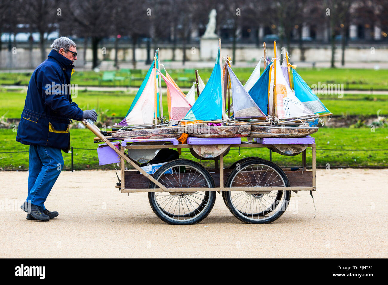 Man with cart carrying toy sailing boats in the Tuileries Gardens, Paris, France Stock Photo