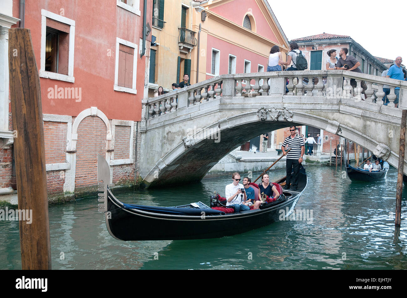 People enjoying ride on gondola on Rio de Palazzo de Canonica Venice Italy near Bridge of Sighs - Stock Image