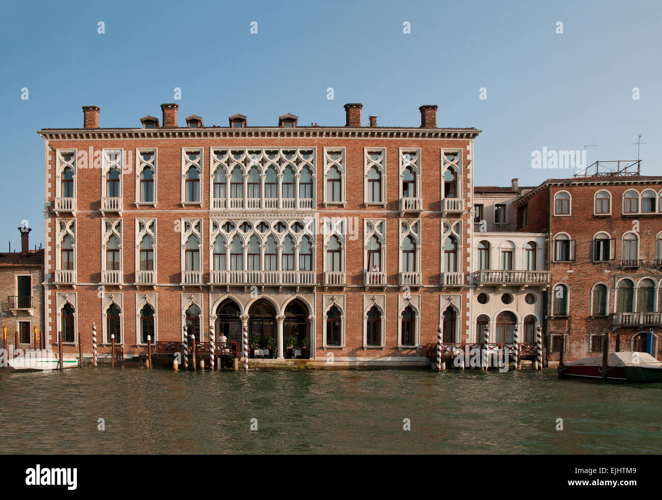 Substantial palace buildings houses palazzo pallazi with moored motor boats on the Grand Canal Venice Italy - Stock Image
