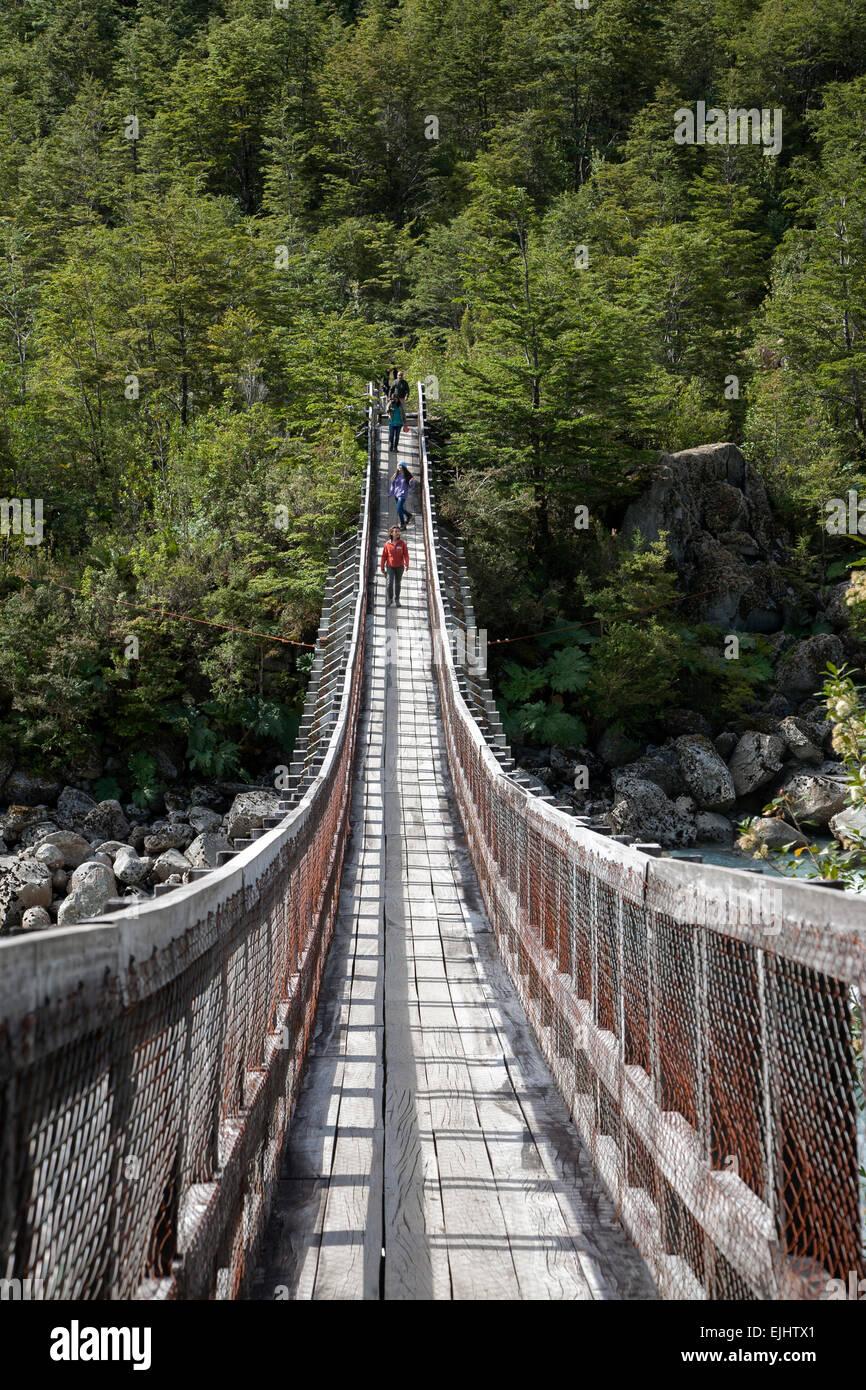 Tourists crossing a suspension bridge. Queulat National Park. Aysén Region. Chile - Stock Image
