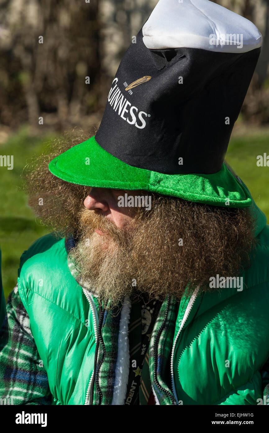 Bearded man in Irish hat and green celebrates St. Patrick's Day in Trafalgar Square, London, England - Stock Image