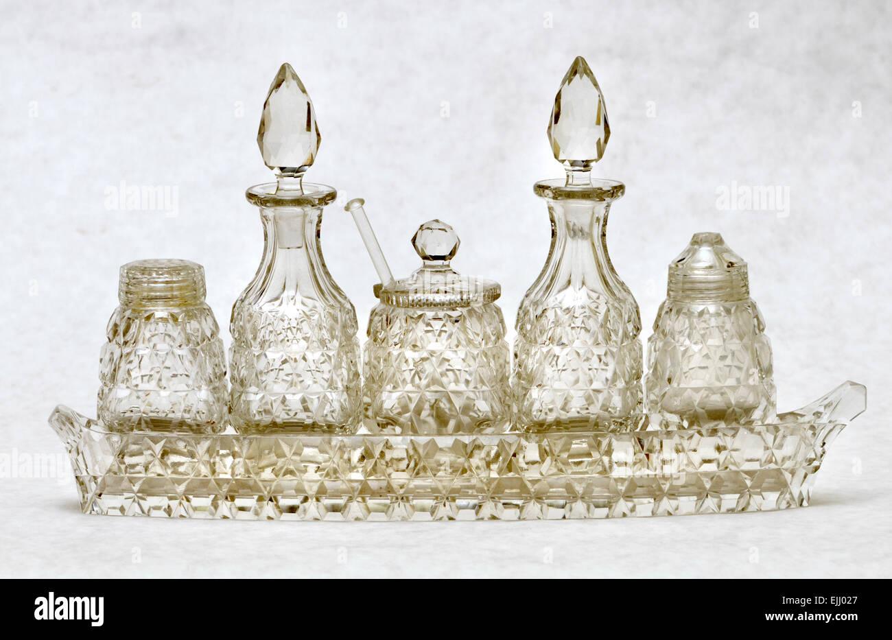 Cut glass cruet set with salt, pepper, mustard, oil and dressing pots - Stock Image