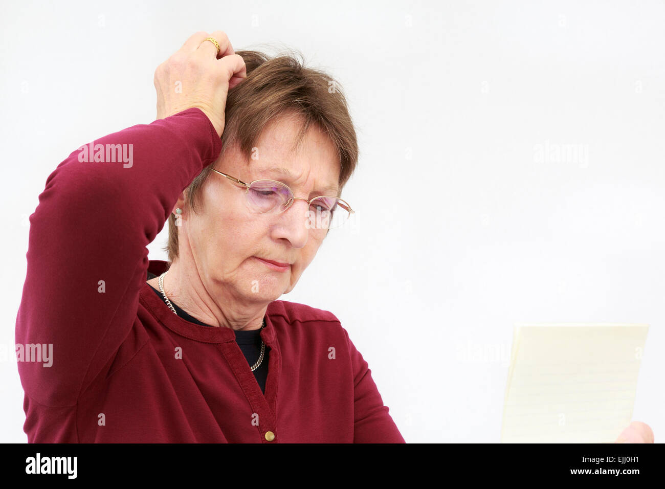 A concerned senior woman scratches her head whilst reading a confusing letter she is holding and thinking. England, - Stock Image