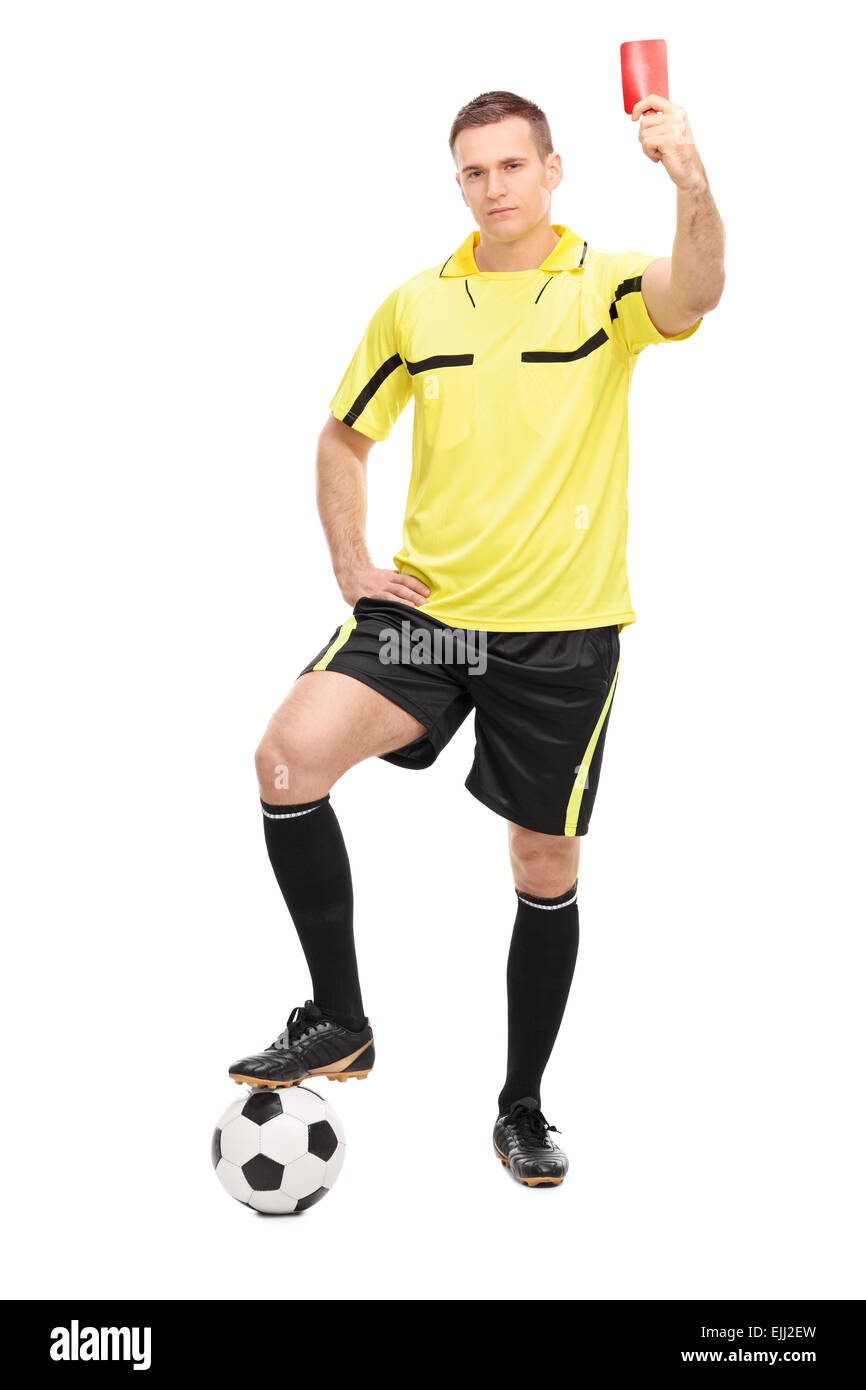 Full length portrait of a strict football referee standing over a ball and showing a red card isolated on white - Stock Image