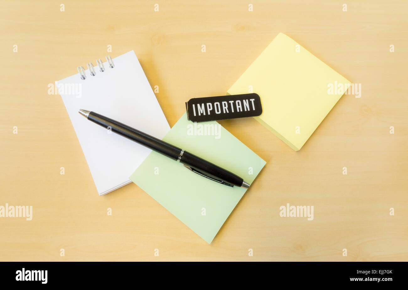 Different Colors of Postit with Important Word and Black Pen on Wood Surface - Stock Image