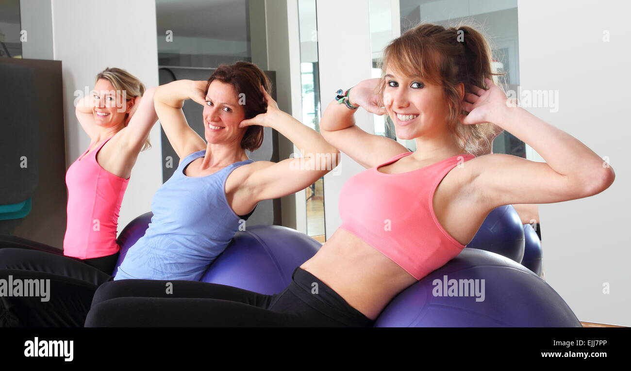 Three women doing exercise on balls in fitness center - Stock Image