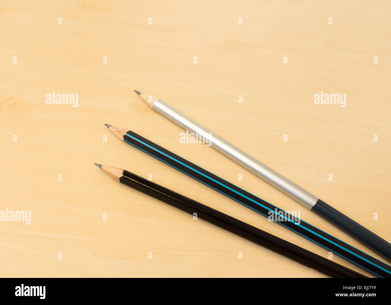 Three Color Sharp Pencils Placed on Light Brown Wooden Table Texture - Stock Image