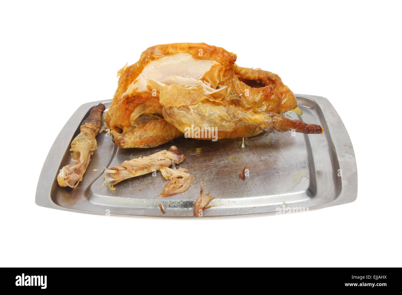 Roast partly carved Guinea fowl on a carving dish - Stock Image
