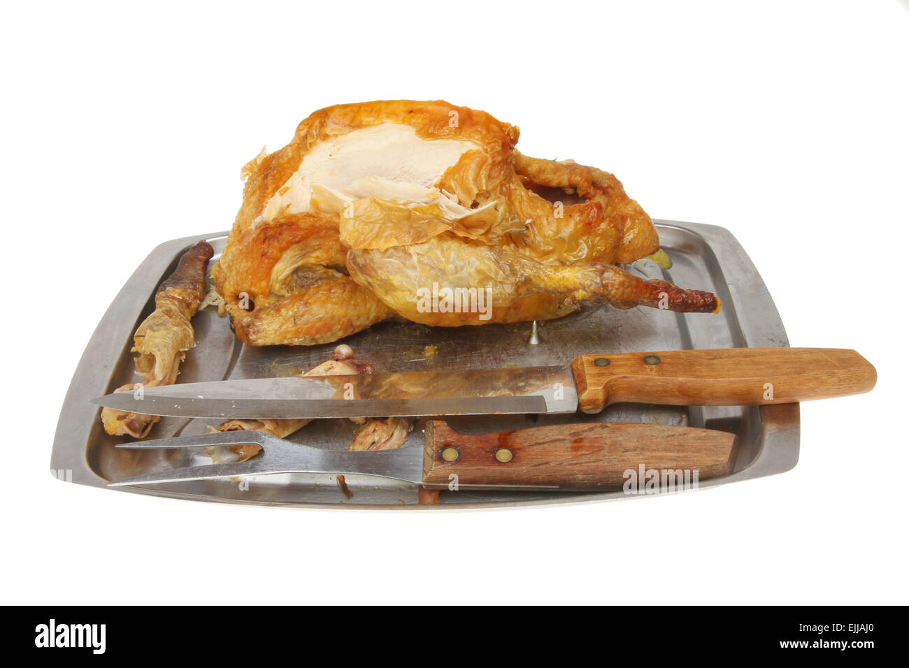 Part carved Guinea fowl on a carving dish with carving knife and fork isolated against white - Stock Image
