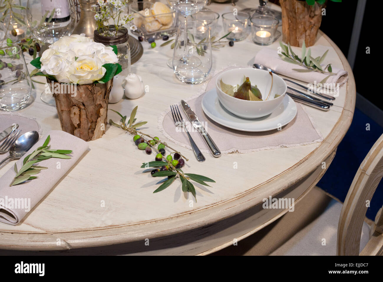 Decoration of wedding table with wooden trunk vases, figs, and olives branch - Stock Image