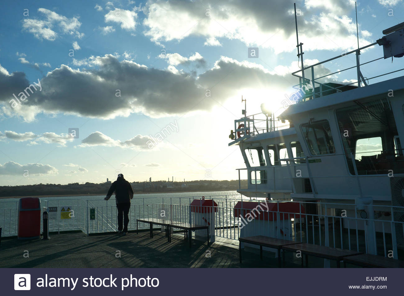 A passenger looks out across the water as the Red Funnel Ferry approaches Southampton port during sunset. Hampshire, - Stock Image
