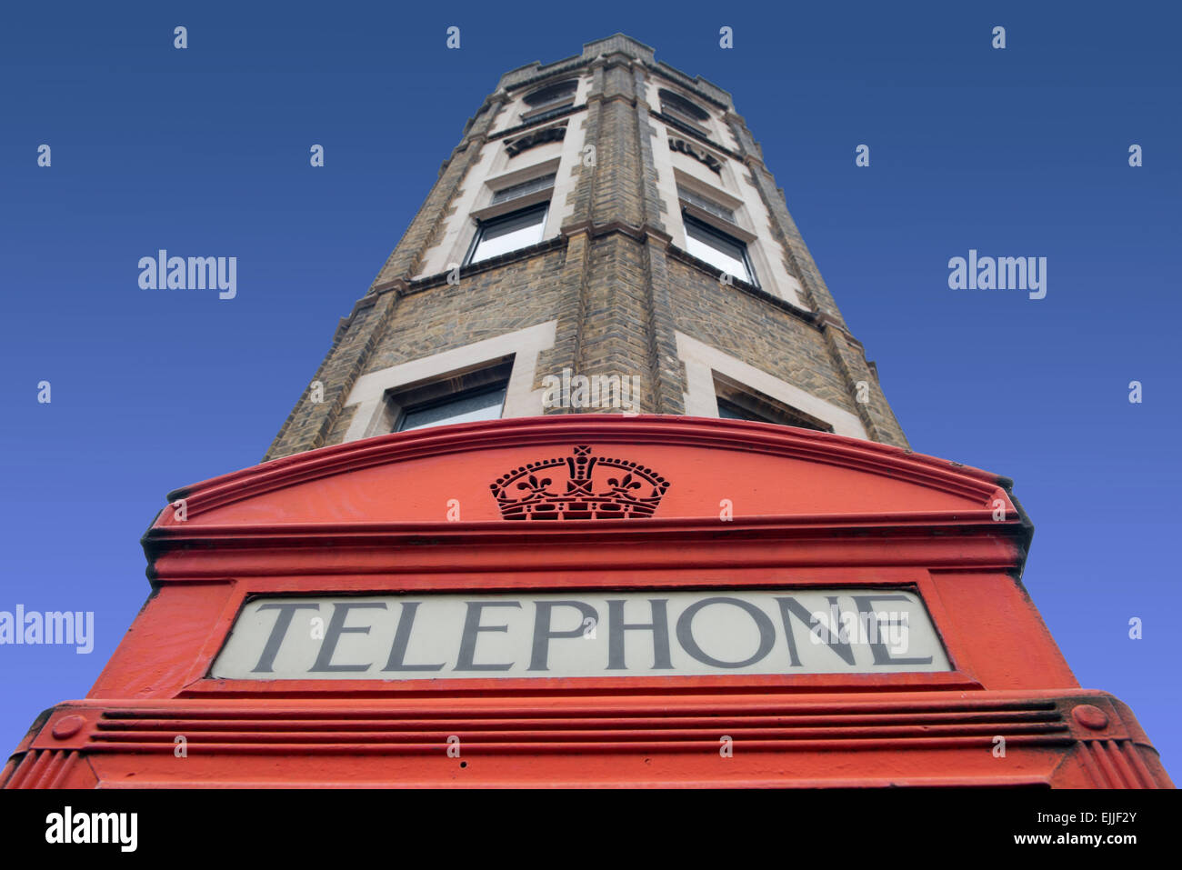 Traditional British red telephone kiosk on the corner of a London Street.  The kiosk is a 1924 design by Giles Gilbert - Stock Image