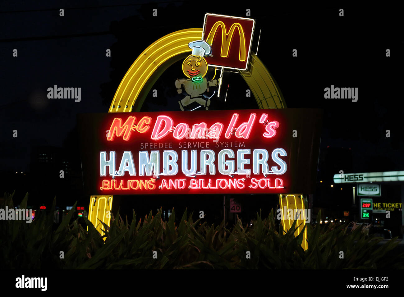 McDonalds fast food restaurant neon hamburger sign, golden arches light sign outside McDonald's exterior - Stock Image