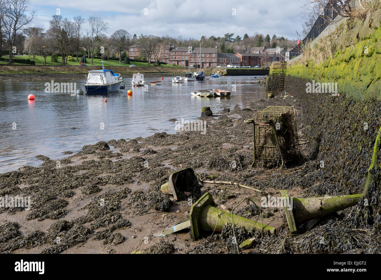 The River Leven, Dumbarton, Scotland, UK at low tide revealing old traffic cones and debris filled shopping trolley. - Stock Image