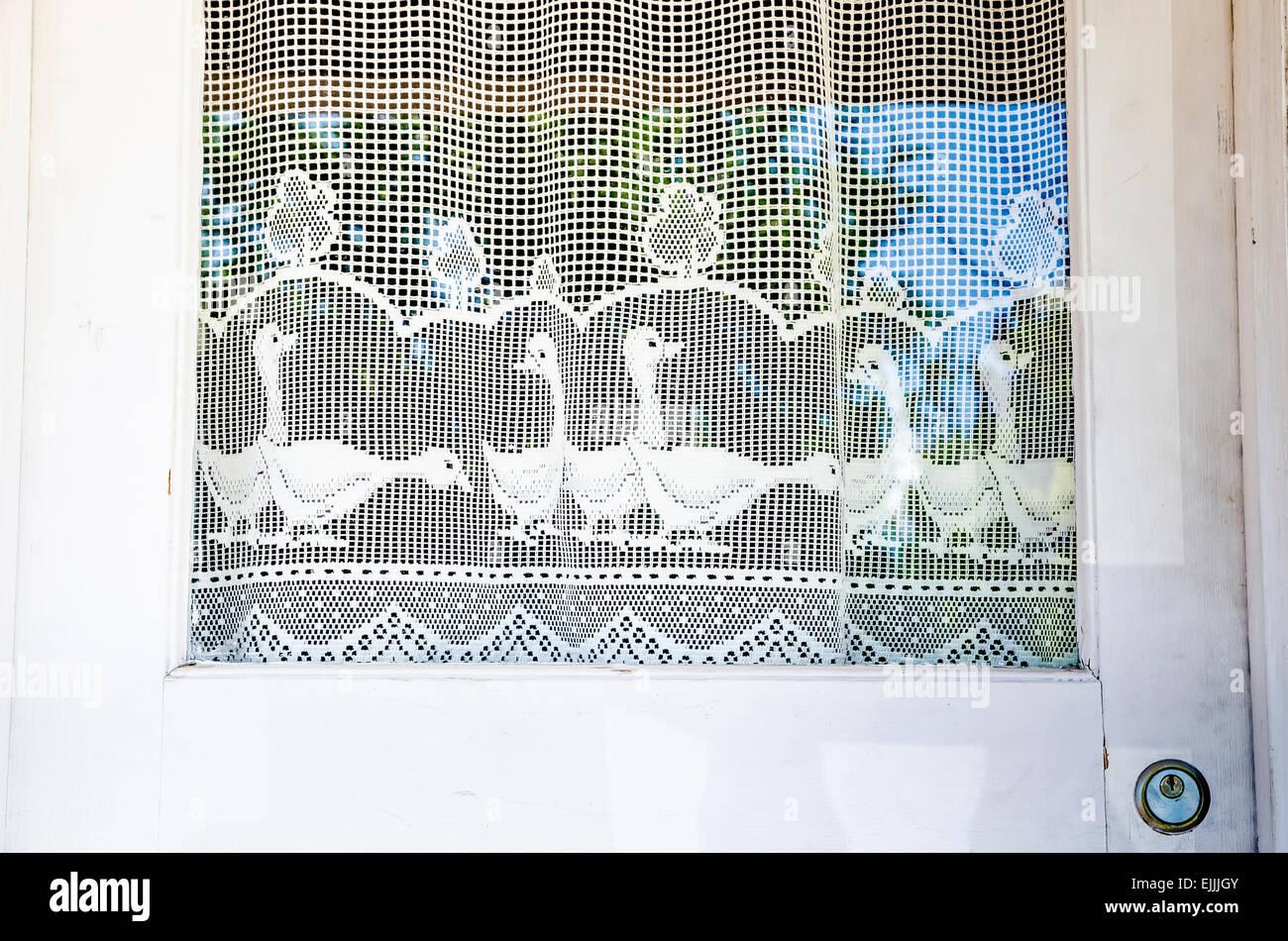 Crochet style linen curtain with ducks on door in Winthrop , Washington, USA - Stock Image