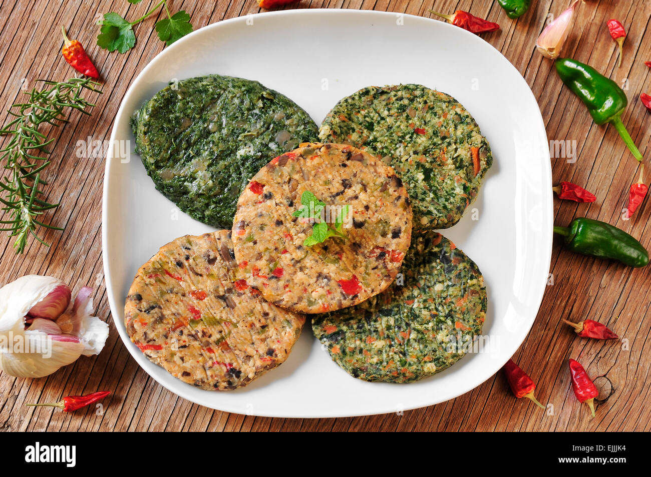 some different raw veggie burgers in a plate on a rustic wooden table - Stock Image