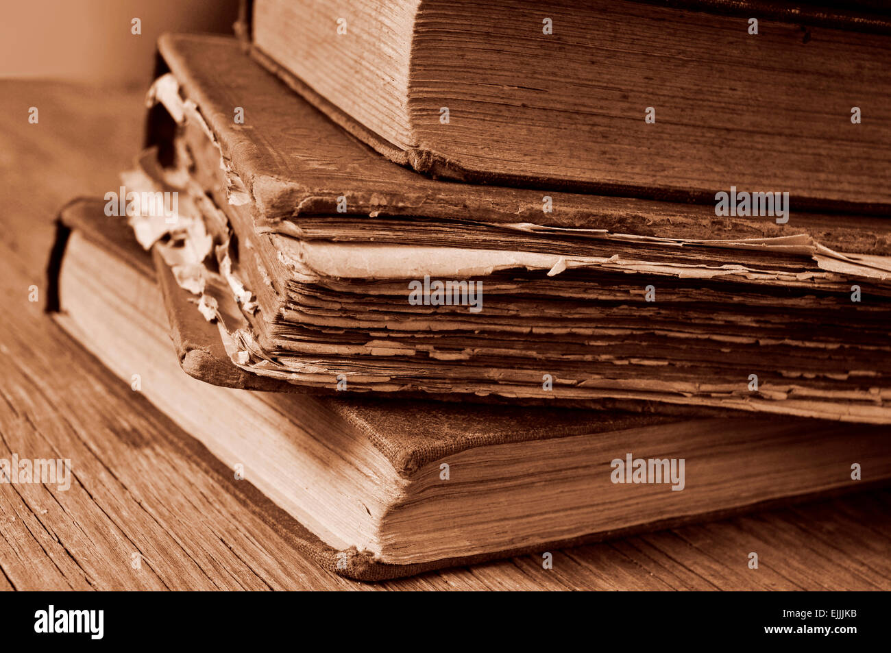 closeup of a pile of worn-out old books on a rustic wooden table, in sepia toning - Stock Image